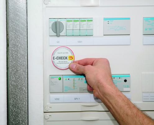E-Check Prüfsiegel wird In Sicherungskasten geklebt